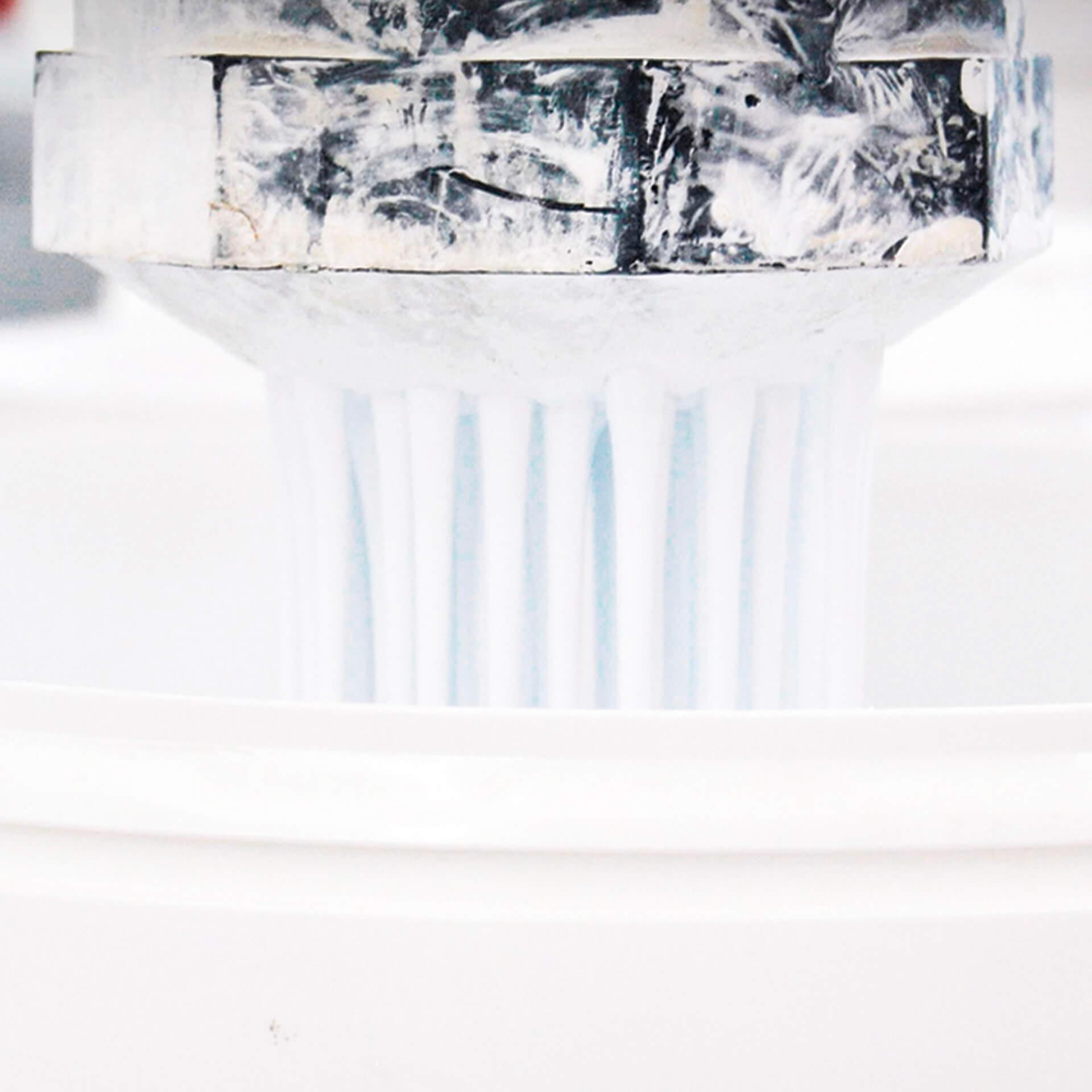 Una máquina rellenando un bote de pintura blanca