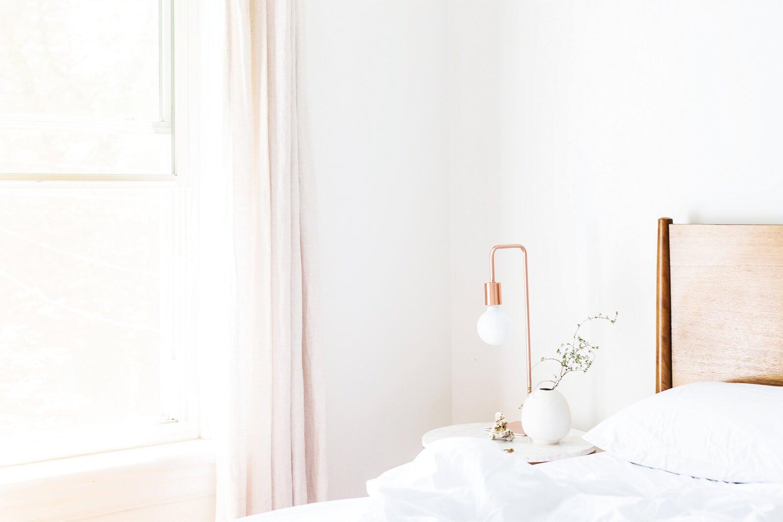 Dormitorio pintado de blanco con detalles en cobre