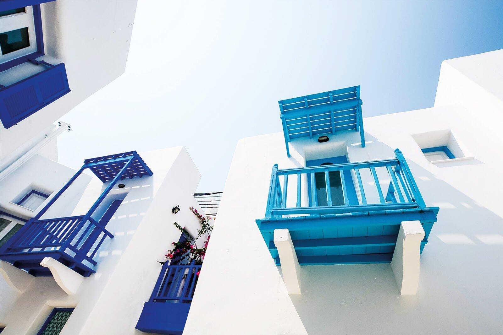 Fachada de una casa pintada de blanco con las ventanas pintadas con pintura azul