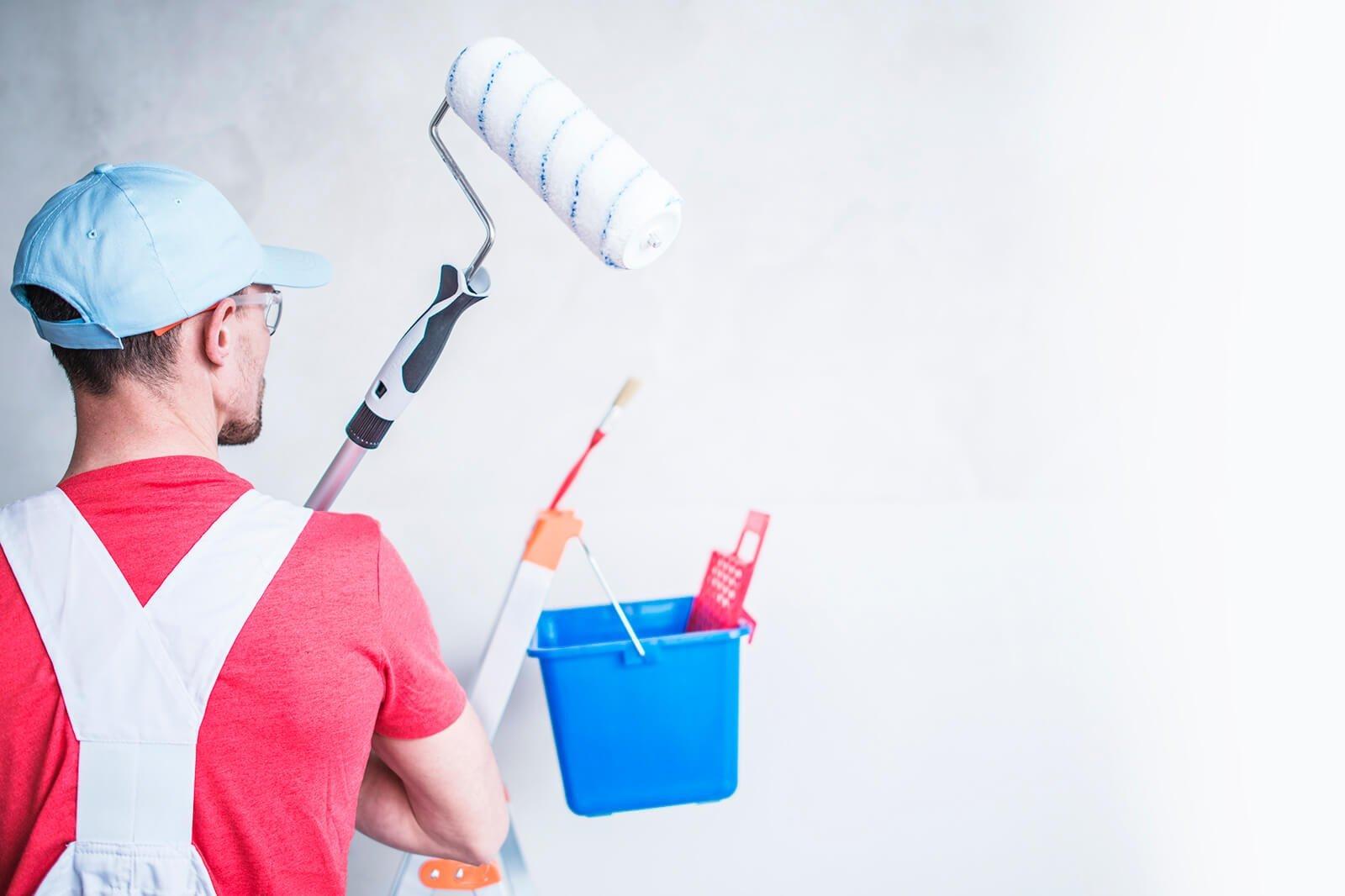 Foto de un pintor de espaldas con un rodillo de pintura y un cubo de pintura de color azul