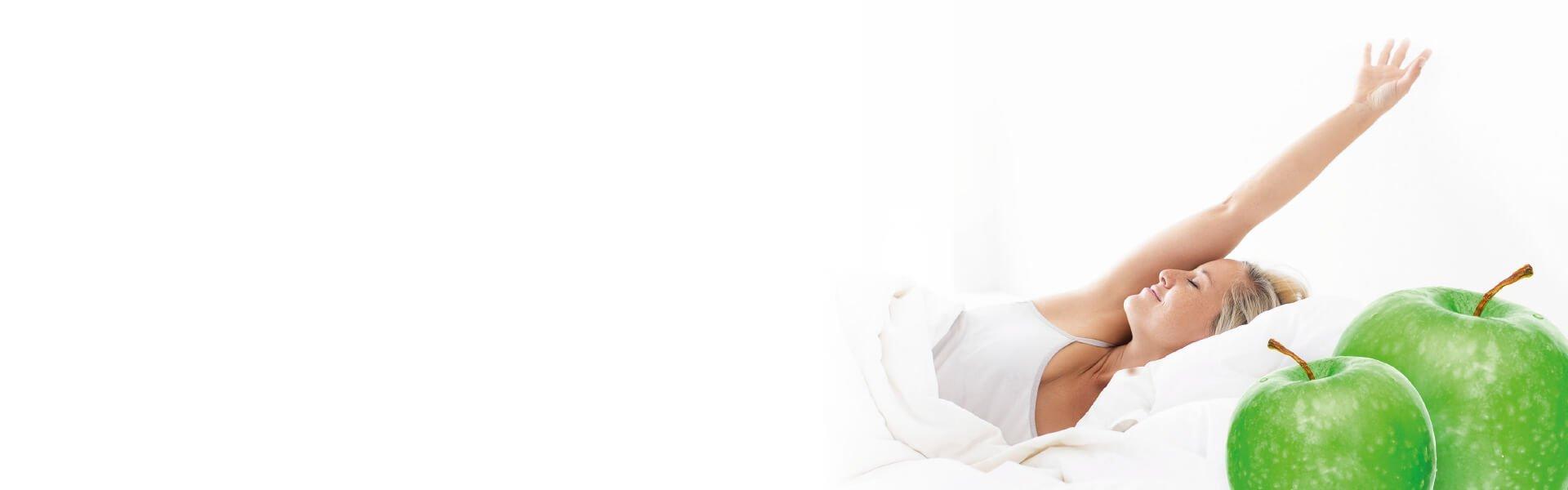 Foto de una mujer en la cama con dos manzanas verdes