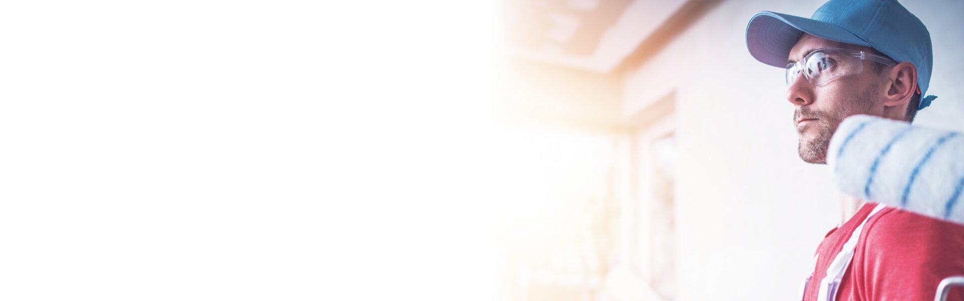 Foto de un hombre con gafas de protección sujetando un rodillo de pintura